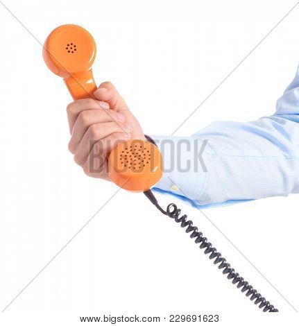 Close-up Of Hand Holding Telephone Receiver Over White Background