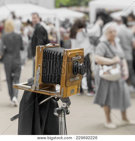 Vintage Photo Wooden Camera On A Tripod Against The Background Of Walking People In Park. Processed