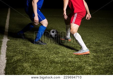 Soccer Player Dribbling The Ball In A Match On Pitch. Footballer Running And Kicking Ball On Sports