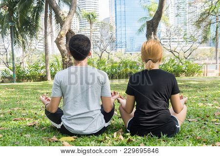 Young Love Couple Making A Meditation To Calm Their Mind After Exercising In Park Encircle With A Wa