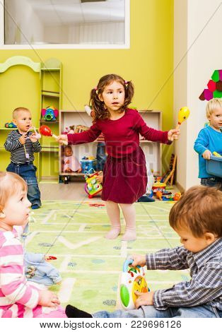 Little Girl In A Red Skirt With Maracas Dancing. Dancing To Rhythmic Music At The Kindergarten