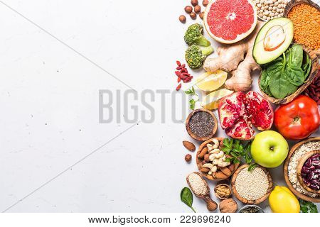 Superfoods On White Background. Organic Food And Healthy Vegan Food. Legumes,  Nuts, Seeds, Greens,