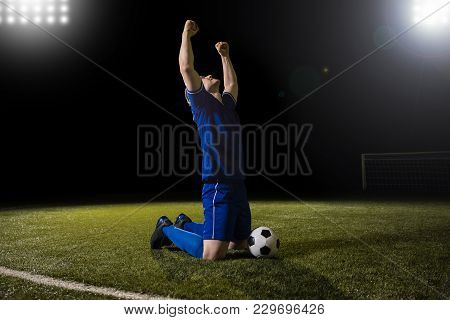 Young Happy And Excited Football Player In Blue Jersey Celebrating Scoring Goal Kneeling On Grass Pi