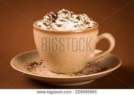 Cooffee Drink Or Cappuccino Cup With Whipped Cream On Brown Background.
