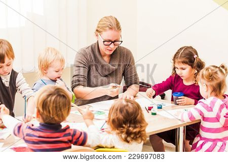 Children And Tutor Are Painting With A Brush And Watercolors On Paper In The Kindergarten