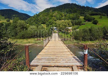 Suspension Bridge Over River. Long Rope Bridge Cross The Stream In The Village