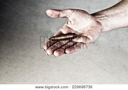 Conceptual Photography Against The War. A Big Bullet In The Hands Of A Girl. Hands In The Dirt.