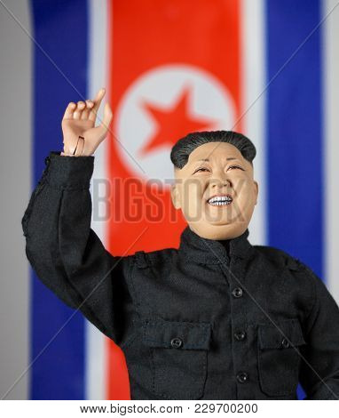 MARCH 4 2018: Caricature of North Korean Supreme Leader Kim Jong Un waving in front of the flag of the Democratic Republic of North Korea