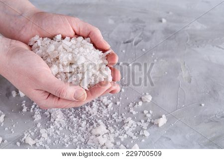 Sea Salt Crystals In Women Hand On White Background, Top View, Close-up. Natural Skin Peeling Hands.