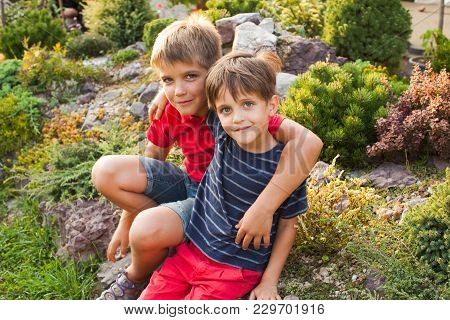 Two Brothers Are Sitting And Hugging Outdoors