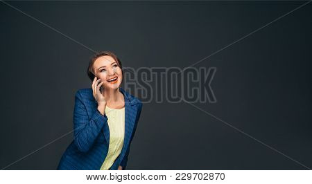 Laughing Business Woman Talking On Her Smart Phone Looking Away While Standing Against Grey Backgrou