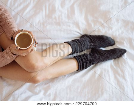 Portrait Of Woman On The Bed With Phone And Cup Of Coffee In Hands. Top View. Cozy Morning.