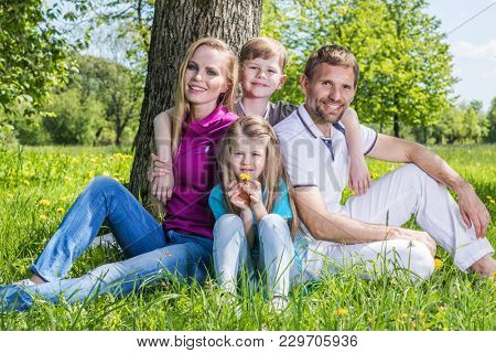 Happy family with man, woman and two children leaning on tree in city park