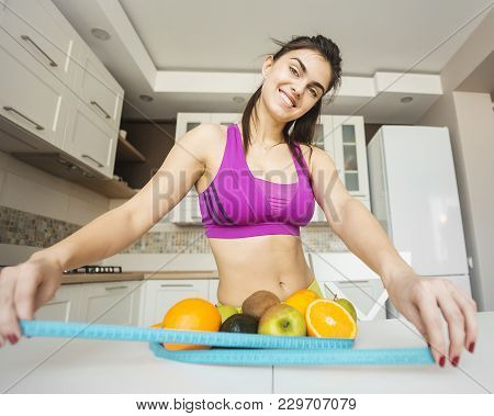 Fitness Girl Putting Meter Around Fruits On White Kitchen Table, Keeping Fit With Healthy Diet Conce