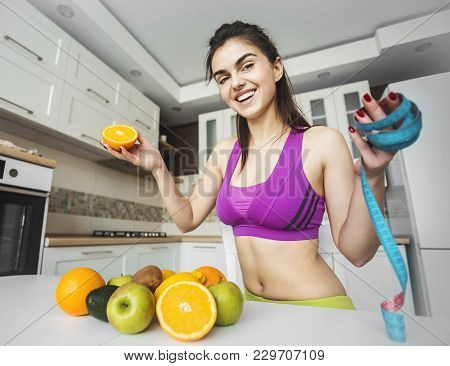 Fitness Girl Near Kitchen Table With Fruit And Meter, Keeping Fit With Healthy Diet Concept