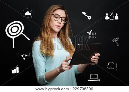 Feeling Interested. Calm Attentive Smart Employer Holding A Convenient Modern Tablet In Her Hands An
