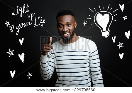 Enjoying Life. Cheerful Positive Young Man Standing Against The Gray Background And Pointing In Fron