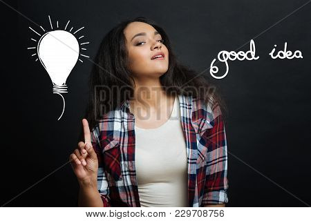 Good Idea. Pretty Emotional Clever Woman Standing Against The Gray Background And Pointing Her Finge