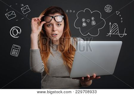 Clever Woman. Calm Smart Young Employee Standing With Her Fingers Touching The Glasses And Looking C