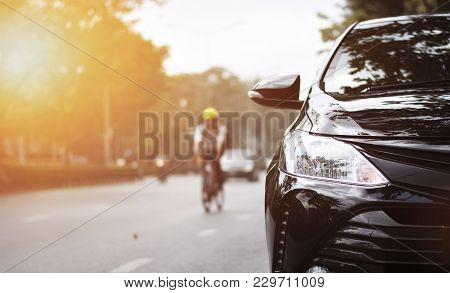 Focusing On The Black Car Headlights On A Street Corner With Sunlight Flares, In The Background, The