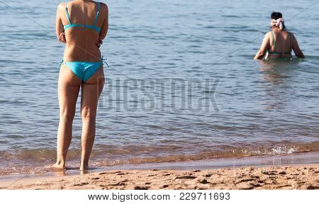Girl In A Bathing Suit On The Beach .