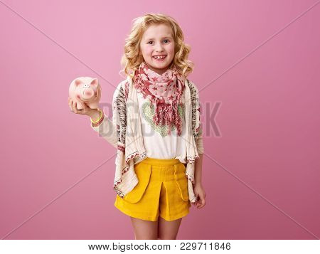 Smiling Modern Child Isolated On Pink Holding Piggy Bank