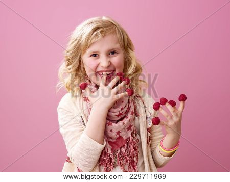 Smiling Child On Pink Background Eating Raspberries On Fingers
