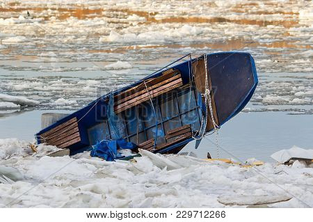 Blue Boat Stacked And Smashed In The Ice Blocks Of Deeply Frozen Danube River.
