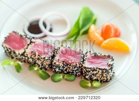 Seared tuna with sesame seeds with green salad on white plate