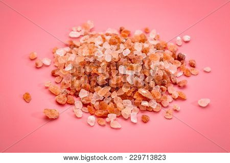 coarse crystals of pink  Himalayan salt, a pile on pink background, top view