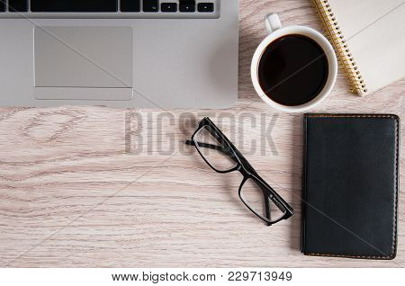 Top View Of Laptop And Notepad With Glasses And Pocketbook On Wood Desktop And Cup Of Coffee.