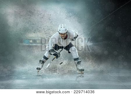 Caucassian ice hockey Player in dynamic action in a professional sport game play around splash drops in hockey under stadium lights.