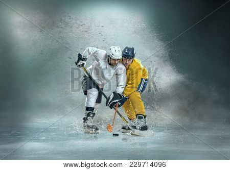 Caucassian ice hockey Players in dynamic action in a professional sport game play around splash drops in hockey under stadium lights.