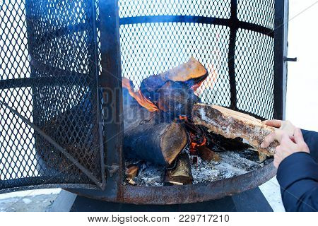Outdoor Metallic Fireplace In Winter Season Charged With Firewood, In The Burning Process. Wood-burn