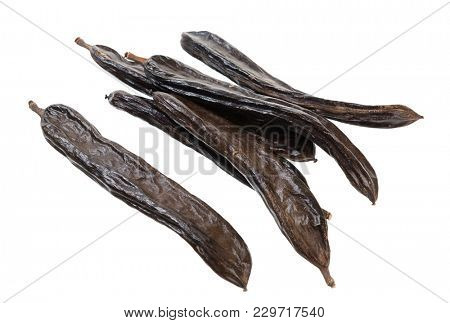 Carob pods in glass jar isolated on white background.