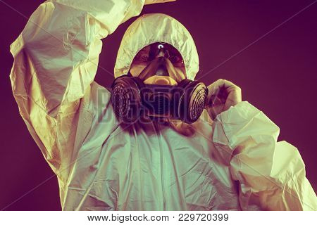 Contagious virus infection concept. Man in protective suit and antigas mask with glasses. Ebola, toxic gases, biological warfare, infections and diseases