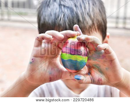 Close Up Of  Asian Boy With Colorful Stained Hands Holding Rainbow Ester Egg To Obscure His Face. Ha