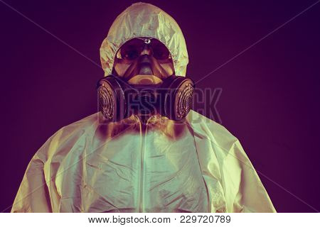 Scientist virus infection concept. Man in protective suit and antigas mask with glasses. Ebola, toxic gases, biological warfare, infections and diseases