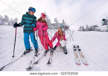 Skiing, winter, snow, sun and fun - mother preparing for skiing her happy children on ski resort