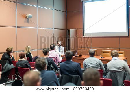 Public Speaker Giving A Talk At Business Meeting. Audience In The Conference Hall. Skilled Coach Ask