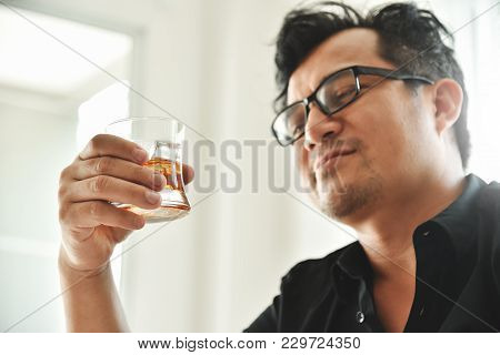 Alcohol Addicted Businessman Is Holding Whiskey Glass While Working. Sad Depressed Patient Male Adul