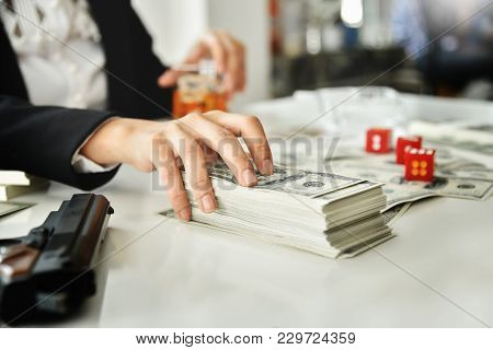 Gambling Concept. Alcohol Addicted Asian Woman In Black Shirt With Dice, Gun And Whiskey Glass. Asia