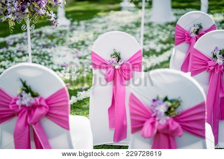 The Wedding Venue, The Chairs With White Lawn Cover Decorated In Pink Theme With The Cone Of Rose An