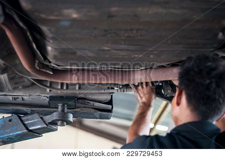 Auto Mechanic Asian Checking Bush-bolt Under Double Wishbone Suspension By Hand With Tools Car Lift