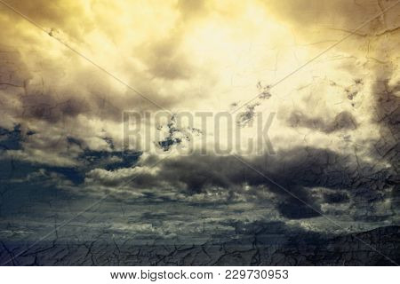 Global warming concept landscape. Dramatic cloudy sky and dry cracked earth