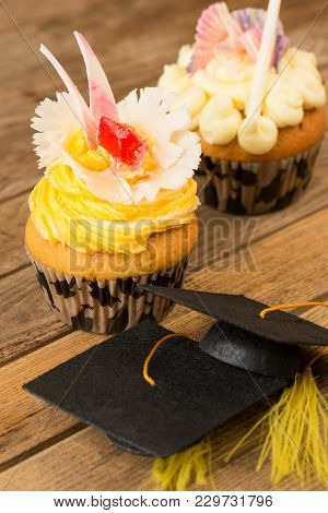 Graduation Cupcakes With Mortarboards On Wooden Table