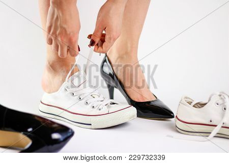 Girl Changing Shoes. Removes Black Shoes And Wears White Sneakers. Tired Feet Of Shoes. Close Up. Is