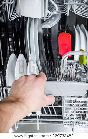 Man Unloads Clean Dishes From The Bottom Basket Of The Dishwasher
