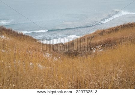 Field Of Dry Grass And Hay In The Ravine And Sea Surf Wave On The Icy Winter Shore. Far East Landsca