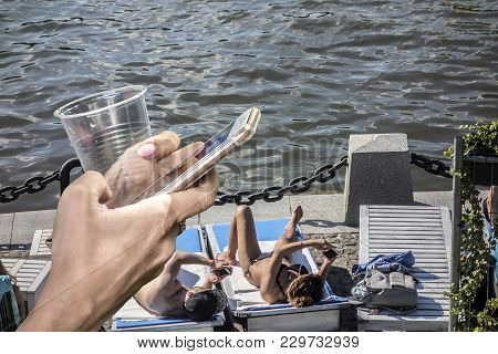 Close-up Of Female Hands Holding A Phone And A Plastic Cup Against The Sea, White Tables And Resting